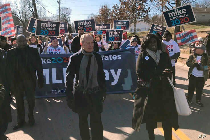 Former New York City Mayor, and Democratic presidential candidate Michael Bloomberg walks with supporters along the route of the Little Rock