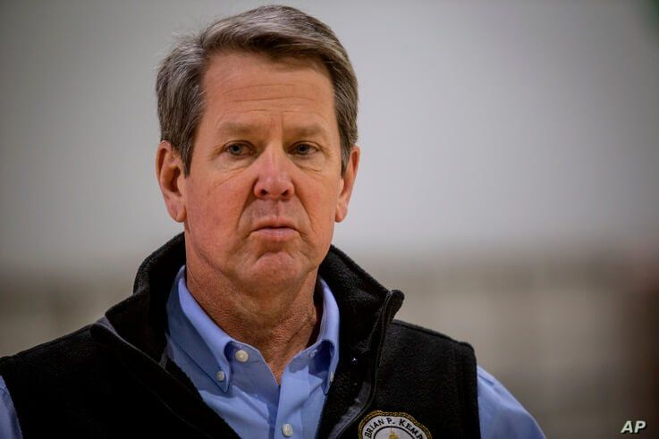Georgia Gov. Brian Kemp listens to a question from the press during a tour of a massive temporary hospital at the Georgia World…