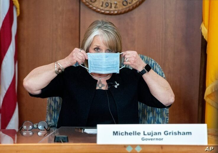 FILE - In this April 15, 2020, file photo, New Mexico Gov. Michelle Lujan Grisham puts on her face mask when not speaking…