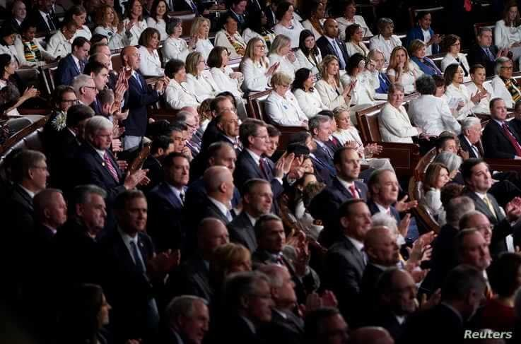 Women members of Congress dressed in white sit behind Republican members applauding President Donald Trump as he delivers the…