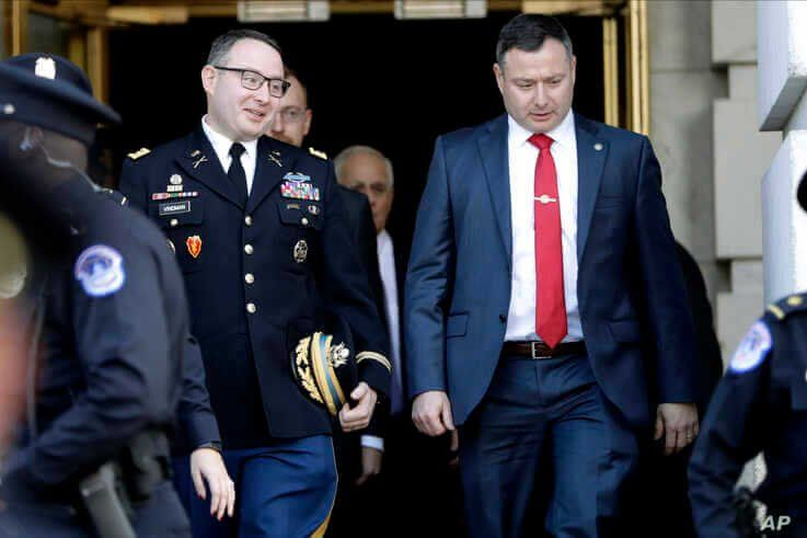 FILE - Lt. Col. Alexander Vindman, left, walks with his twin brother, Yevgeny Vindman, after testifying before the House Intelligence Committee, on Capitol Hill in Washington, Nov. 19, 2019.