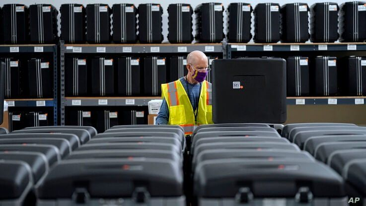 FILE - In this Sept. 3, 2020, file photo, a worker prepares tabulators for the upcoming election at the Wake County Board of…
