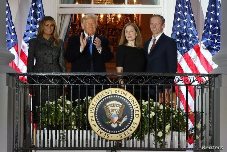 U.S. Supreme Court Associate Justice Amy Coney Barrett poses with first lady Melania Trump, President Donald Trump