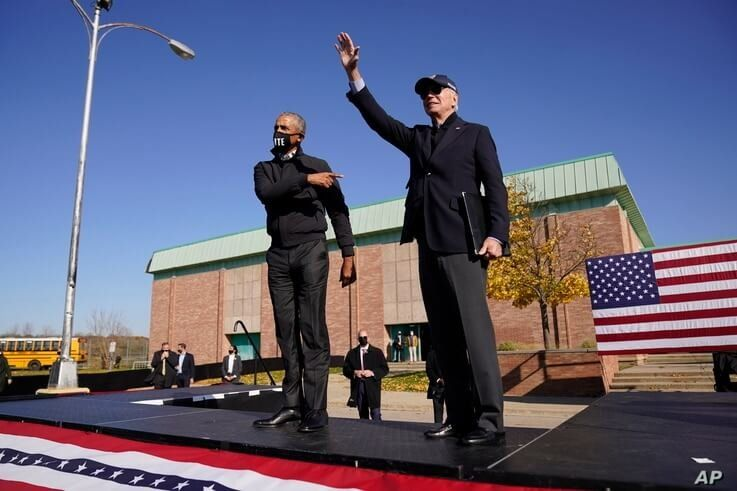 Democratic presidential candidate former Vice President Joe Biden, right, and former President Barack Obama greet supporters at a rally at Northwestern High School in Flint, Michigan, Oct. 31, 2020.