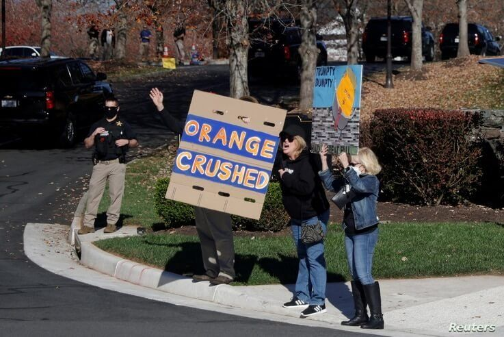 Supporters of President-Elect Joe Biden display signs of protest as the motorcade of U.S. President Donald Trump arrives at the…