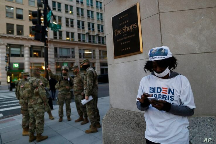 A Biden-Harris supporter stands at a corner as National Guards deploy around the city ahead of President-elect Joe Biden's…