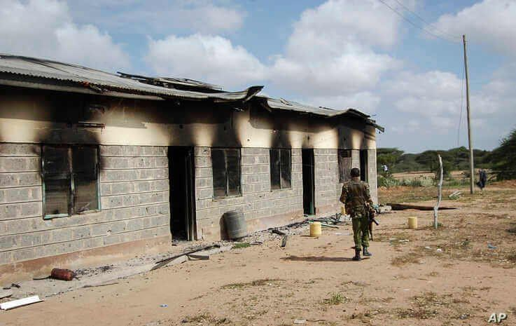 A member of Kenya's security forces walks past a damaged police post after an attack by al-Shabab extremists in the settlement…