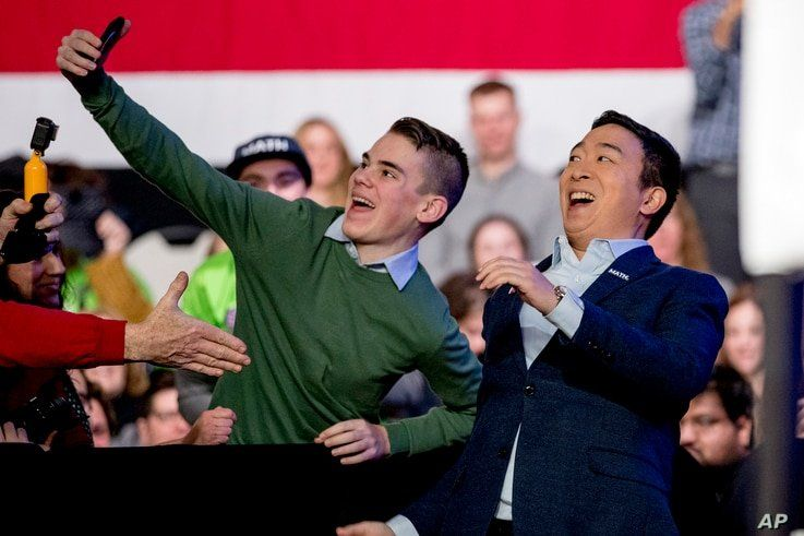 Democratic presidential candidate Andrew Yang takes a photograph with a member of the audience as he arrives at