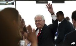 FILE - Outgoing Secretary of State Rex Tillerson waves goodbye as he walks out of the doors of the State Department in Washington, March 22, 2018, after speaking to employees upon his departure.