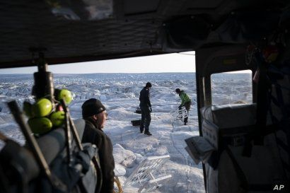 In this Aug. 16, 2019, photo, NYU air and ocean scientist David Holland and field safety officer Brian Rougeux are helped by pilot Martin Norregaard as they carry antennas out of a helicopter at the Helheim glacier, in Greenland.