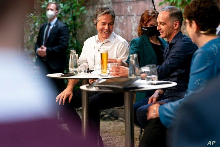 Secretary of State Antony Blinken, left, and German Minister of Foreign Affairs Heiko Maas, right, are served beers as they…