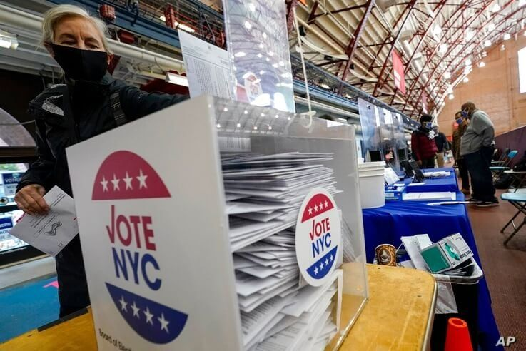 A voter drops off her absentee ballot during early voting at the Park Slope Armory YMCA, Tuesday, Oct. 27, 2020, in the…