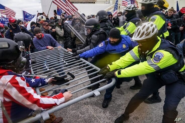 Supporters of President Donald Trump try to break through a police barrier at the Capitol in Washington, Jan. 6, 2021.