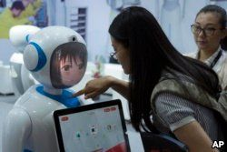 Women interact near a robot designed by Chinese robotics company Pangolin at the Consumer Electronics Show Asia 2018 in Shanghai, China on June 15, 2018.