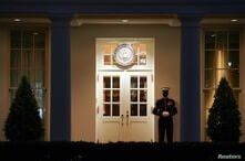 A U.S. Marine stands guard at the entrance to the West Wing as nighttime descends upon the White House in Washington.