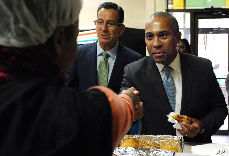 Massachusetts Gov. Deval Patrick, right, shakes hands with bakery employees as Gov. Dannel P. Malloy, center, looks on, during…