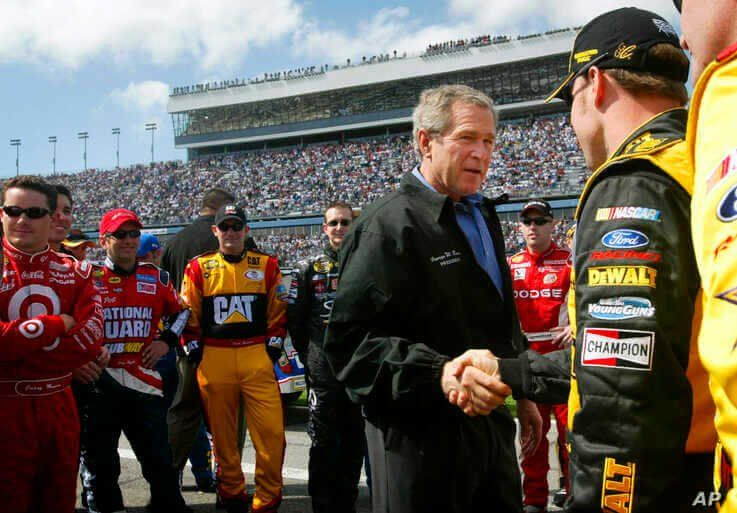 FILE - In this Feb. 15, 2004, file photo, President George W. Bush, left, greets Matt Kenseth, right, as he greets drivers in…