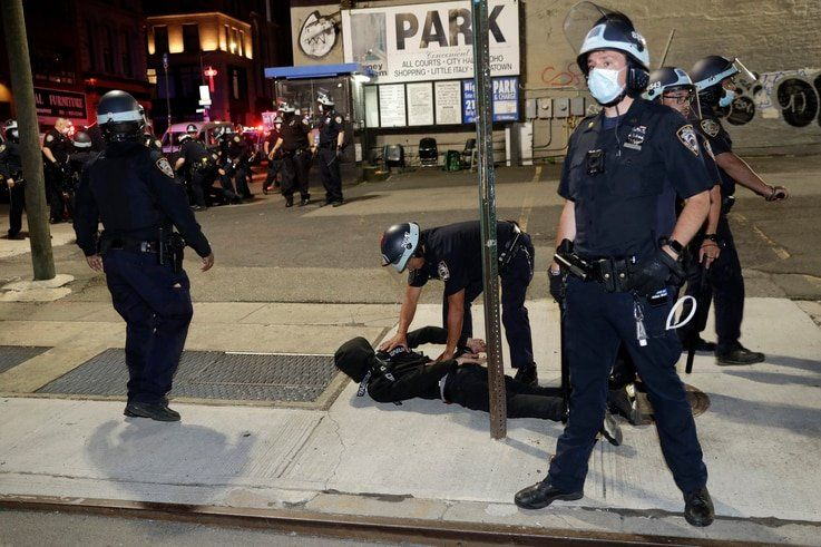 FILE - Police officers cuff a suspect during a protest against police brutality, in New York City, June 1, 2020.