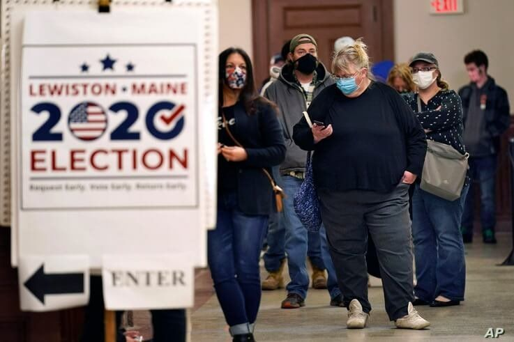 Residents wait to cast their absentee ballots during early voting, Friday, Oct. 30, 2020, in Lewiston, Maine. (AP Photo/Robert…