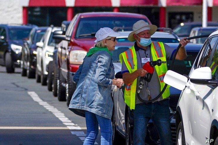 A customer helps pumping gas at Costco, as other wait in line, on Tuesday, May 11, 2021, in Charlotte, N.C. Colonial Pipeline,…