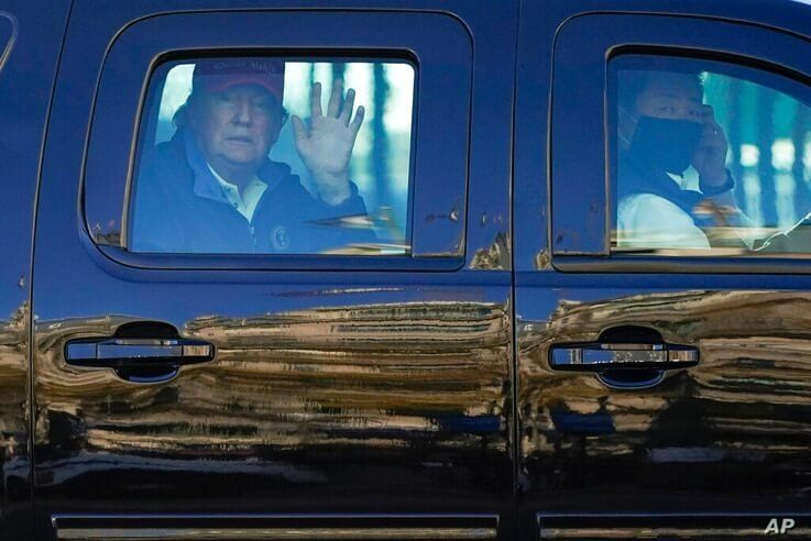 President Donald Trump waves to supporters from his motorcade as people gather for a march Saturday, Nov. 14, 2020, in…