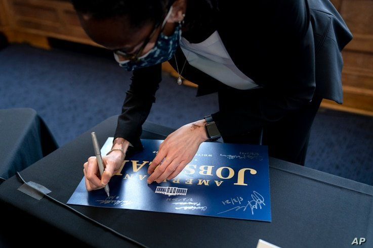 Kim Lewis, Associate Dean for Research and Graduate Programs at Howard University autographs an American Jobs Plan sign after…