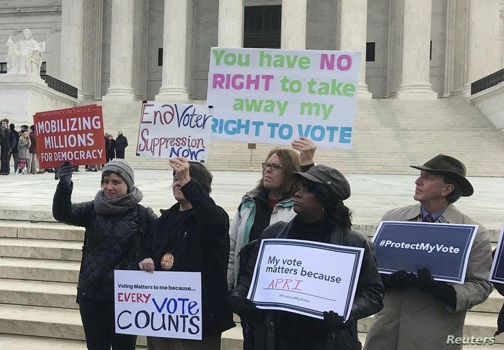 Activists rally outside the U.S. Supreme Court ahead of arguments in a key voting rights case involving a challenge to Ohio's policy of purging infrequent voters from voter registration rolls, in Washington, Jan. 10, 2018.