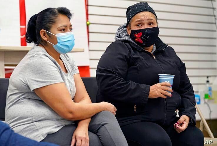 Graciela Uraga, left, a cleaning lady, and Blanca Cedillos, a nanny, react as they watch Joe Biden's presidential inauguration…