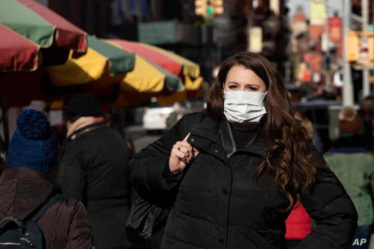 A woman, who declined to give her name, wears a mask in New York, Jan. 30, 2020. She works for a pharmaceutical company and said she wears the mask out of concern for the coronavirus.