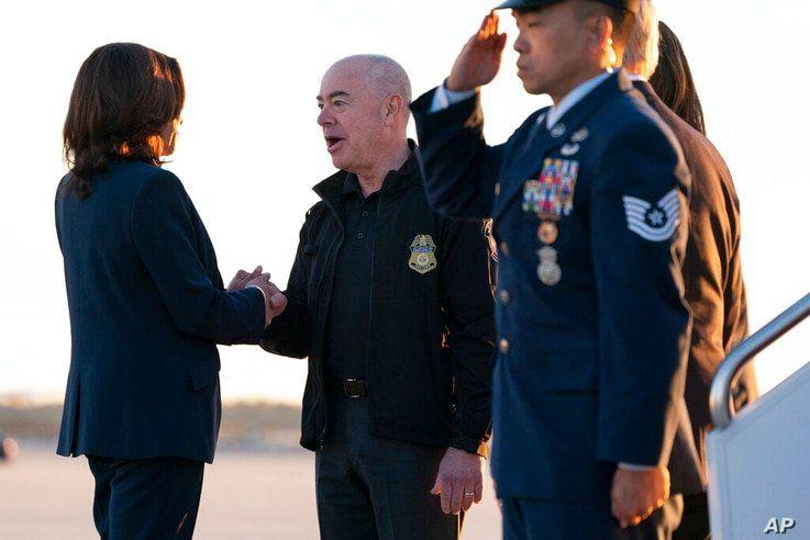 Vice President Kamala Harris greets Homeland Security Secretary Alejandro Mayorkas as she arrives to board Air Force Two,…