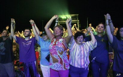 Audience members join hands in worship at the Franklin Graham Decision America event at the Pitt County Fairgrounds in…