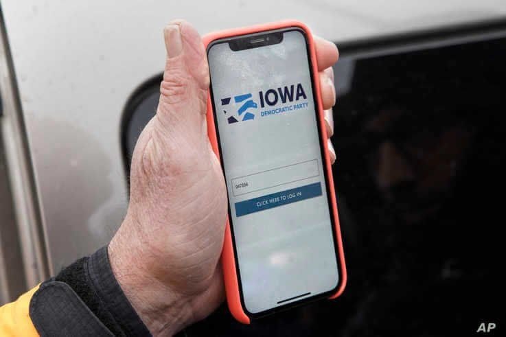 Precinct captain Carl Voss of Des Moines displays the Iowa Democratic Party caucus reporting app on his phone outside of the…
