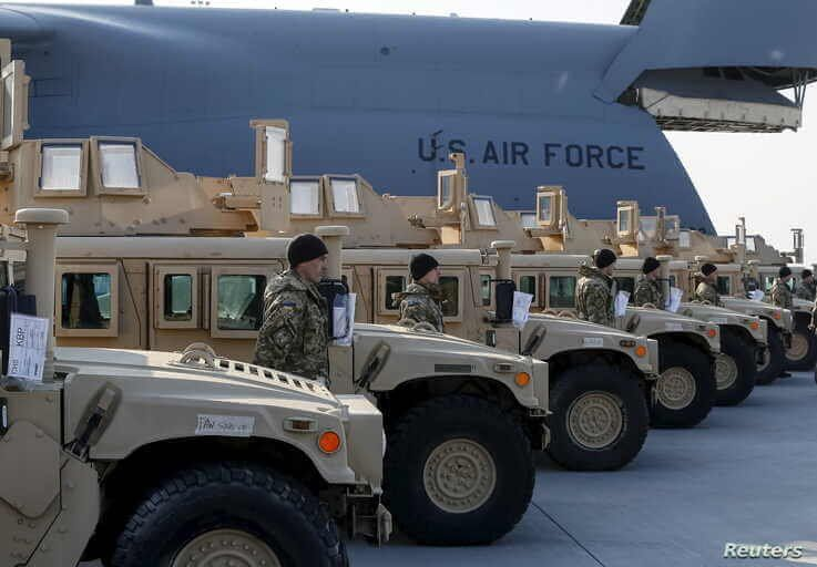 Ukrainian servicemen are seen after a welcome ceremony for the first plane from United States with non-lethal aid including ten Humvee vehicles at Borispol airport near Kyiv, March 25, 2015.