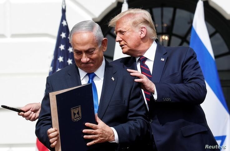 Israel's Prime Minister Benjamin Netanyahu stands with U.S. President Donald Trump after signing the Abraham Accords,…