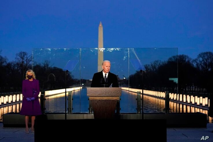 President-elect Joe Biden speaks during a COVID-19 memorial, with lights placed around the Lincoln Memorial Reflecting Pool,…