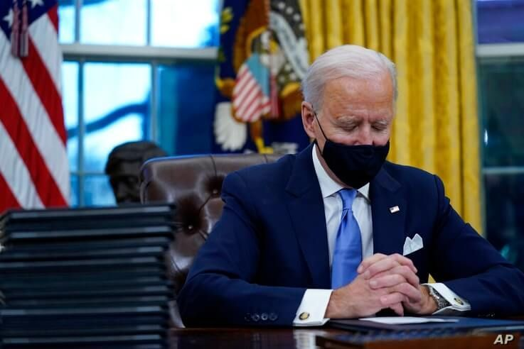 President Joe Biden pauses as he signs his first executive orders in the Oval Office of the White House on Wednesday, Jan. 20,…