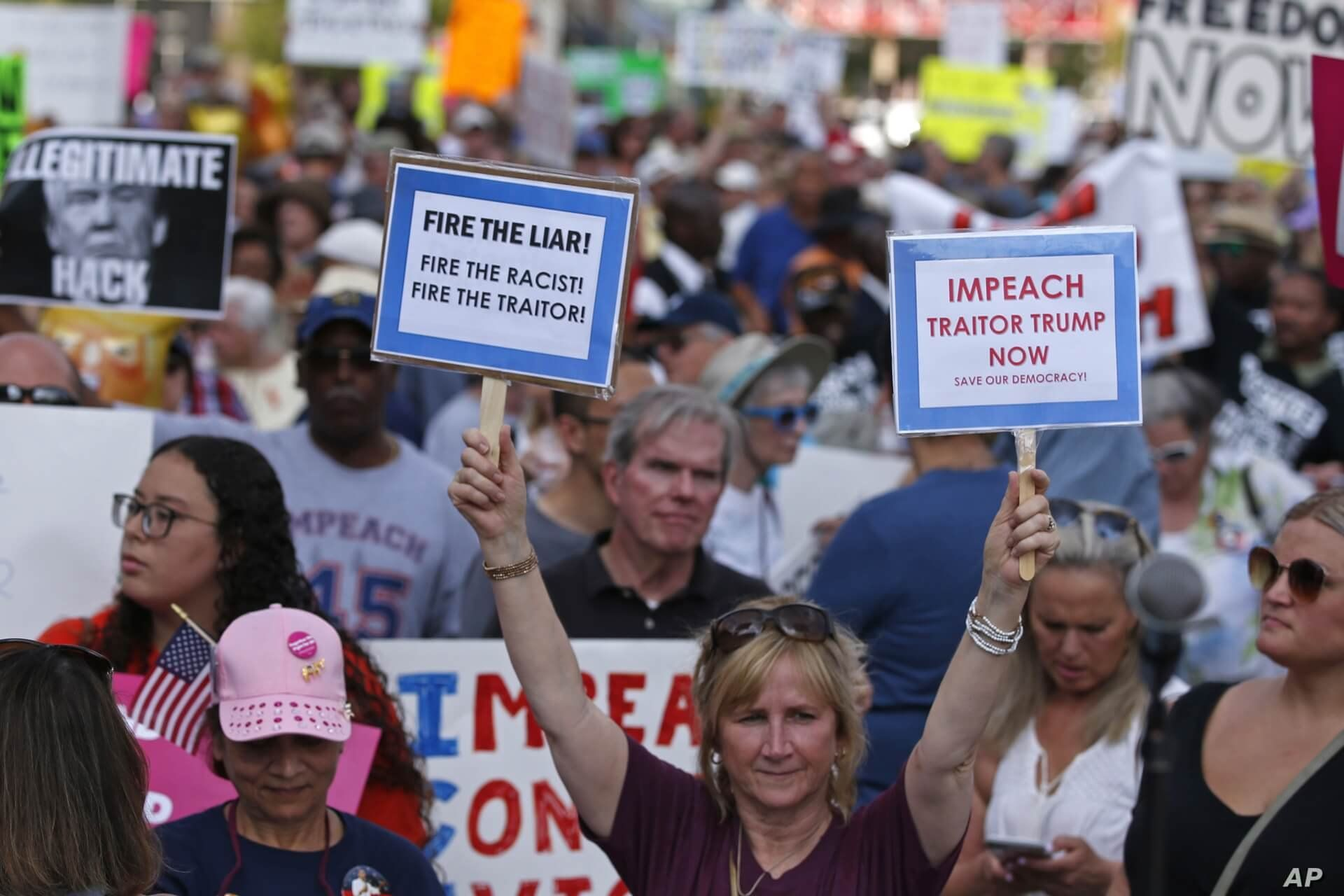Protesters hold signs during a