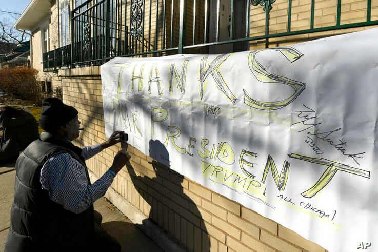 A supporter of former Illinois Gov. Rod Blagojevich makes a sign thanking President Trump at the Blagojevich home Tuesday, Feb…