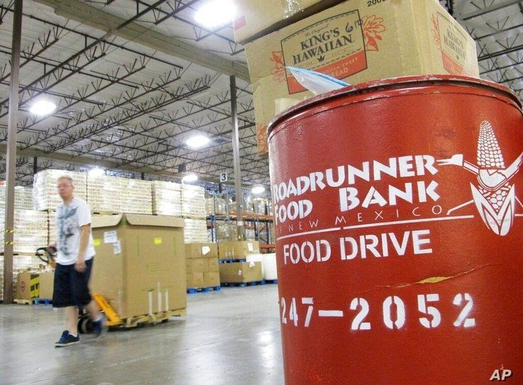 FILE - In this June 21, 2013 file photo a volunteer moves a pallet of food at the Roadrunner Food Bank in Albuquerque, N.M. The…