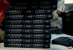 """Politics and Prose bookstore staff members hands out former FBI director James Comey's book during a stop on his book tour for """"A Higher Loyalty,"""" April 30, 2018, in Washington."""