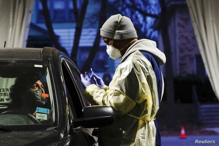 Certified nursing assistant (CNA) Jermaine LeFlore prepares to take a patient's nasal swab at a drive-thru testing site outside the Southside Health Center in Milwaukee, Wisconsin, Oct. 21, 2020.