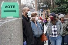 Voters masked against coronavirus line up at Riverside High School for Wisconsin's primary election Tuesday April 7, 2020, in…
