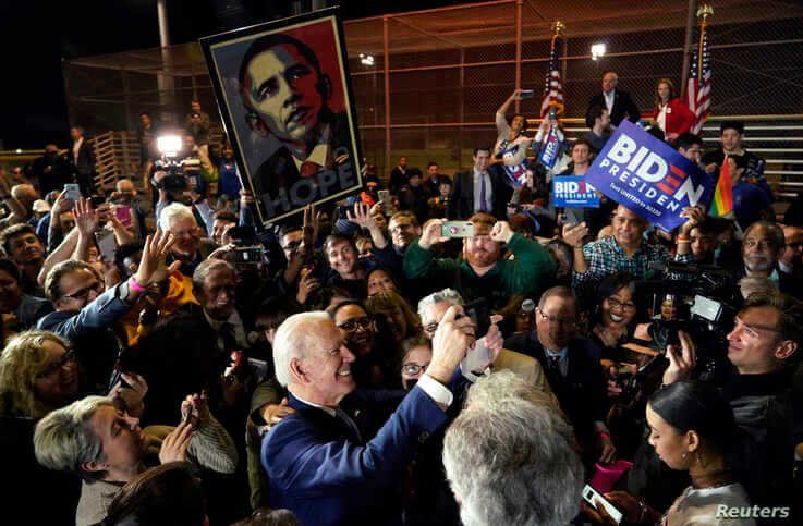Democratic U.S. presidential candidate and former Vice President Joe Biden takes a picture as supporters hold up a