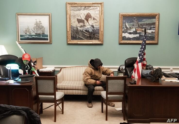 Supporters of US President Donald Trump sit inside the office of US Speaker of the House Nancy Pelosi as he protest inside the…