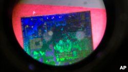 A Chinese microchip is seen through a microscope set up at the booth for the state-controlled Tsinghua Unigroup project which is driving China's semiconductor ambitions during the 21st China Beijing International High-tech Expo in Beijing, China, May 17, 2018.
