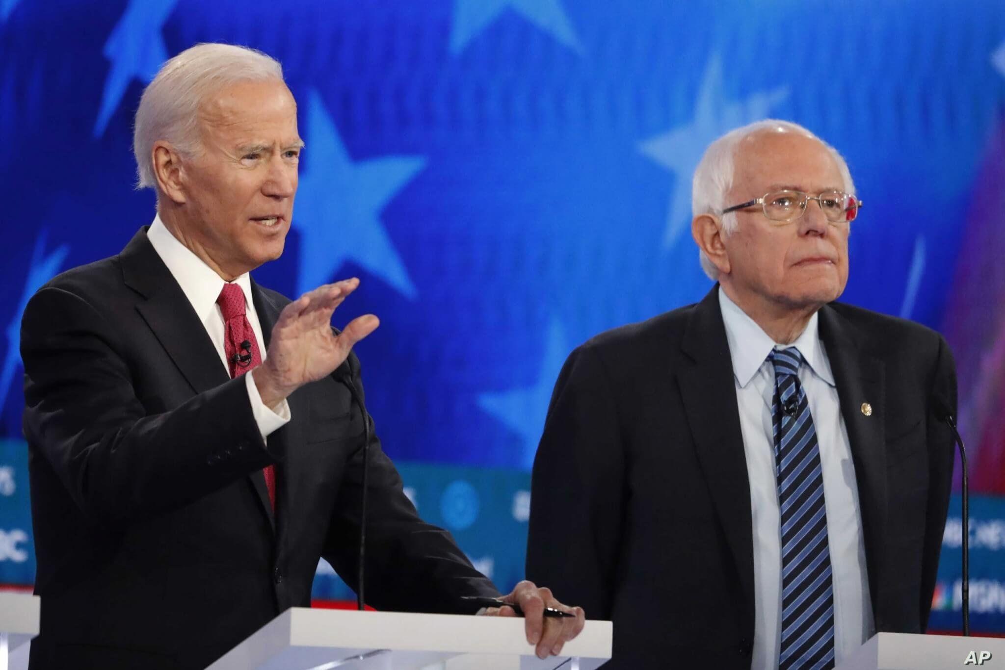 Democratic presidential candidate former Vice President Joe Biden, left, speaks as rival Sen. Bernie Sanders listens