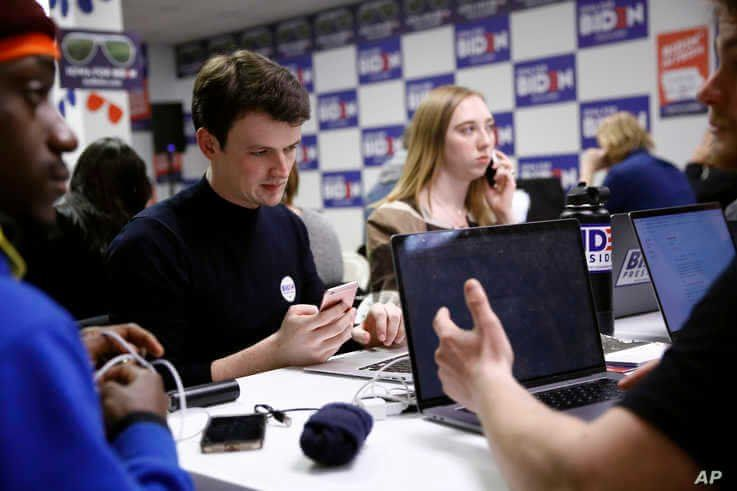 Volunteers call potential caucus-goers at a campaign field office for Democratic presidential candidate former Vice President…