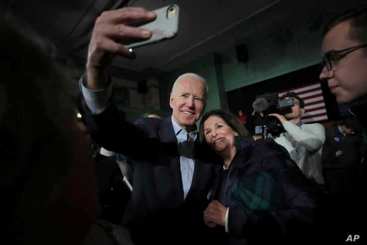 Democratic presidential candidate former Vice President Joe Biden smiles as he takes a selfie during a campaign stop in Exeter,…