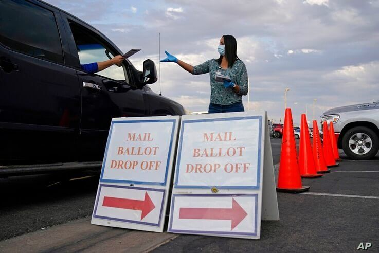 FILE - In this Nov. 2, 2020, file photo, a county worker collects mail-in ballots in a drive-thru mail-in ballot drop off area…