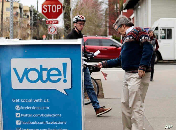 Voters drop off ballots in the Washington State primary, Tuesday, March 10, 2020 in Seattle. Washington is a vote by mail state…